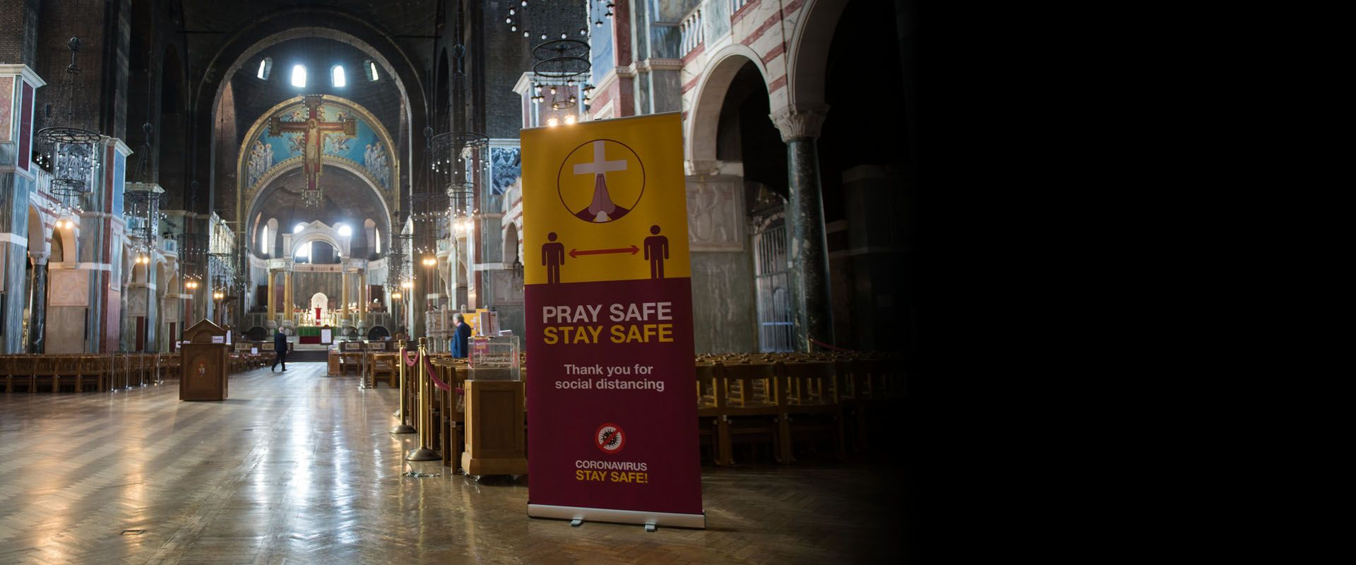 A 'Pray safe, Stay Safe' banner in a Catholic church.